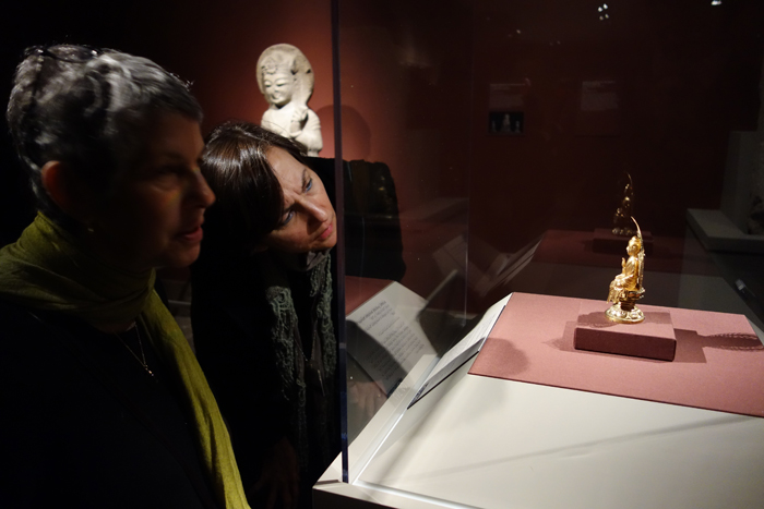 Visitors admire a golden seated Buddha. (photo courtesy of the National Museum of Korea)